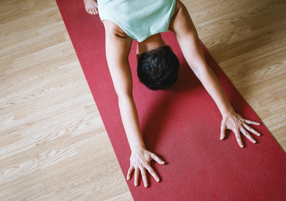 Person practicing downward facing dog on yoga mat